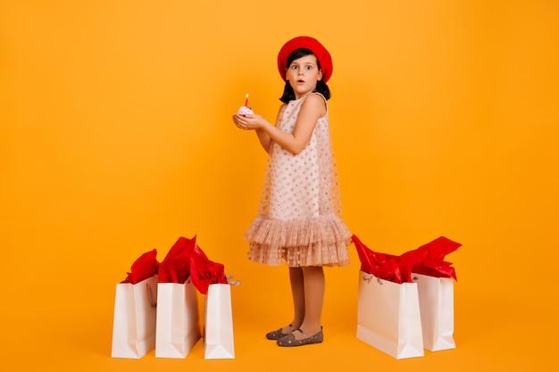 Volle länge des kleinen mädchens mit einkaufstüten. süßes kind in der roten französischen baskenmütze lokalisiert auf gelber wand.