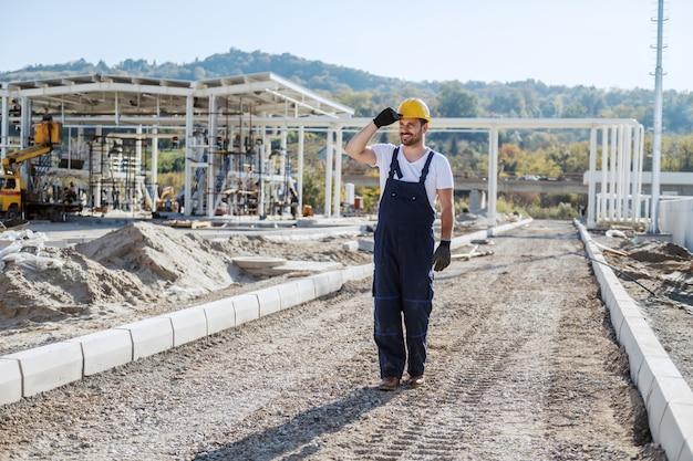 Volle länge des lächelnden positiven kaukasischen arbeiters in overalls und mit helm auf dem kopf gehend. raffinerie außen.