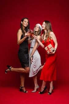 Volle länge des lächelns hübsche drei freundinnen, die gläser mit champagner klirren, lokalisiert auf roter wand