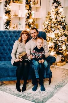 Volle länge des liebenden paares, das auf vintage blaue couch oder liebessitz umarmt