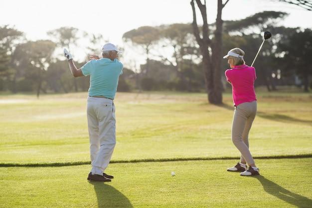 Volle länge des männlichen golfspielers, der frau unterrichtet