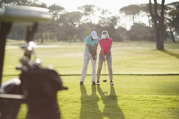 Volle länge des mannes, der frau lehrt, golf zu spielen