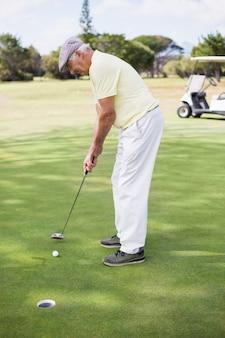 Volle länge des mannes, der golf spielt