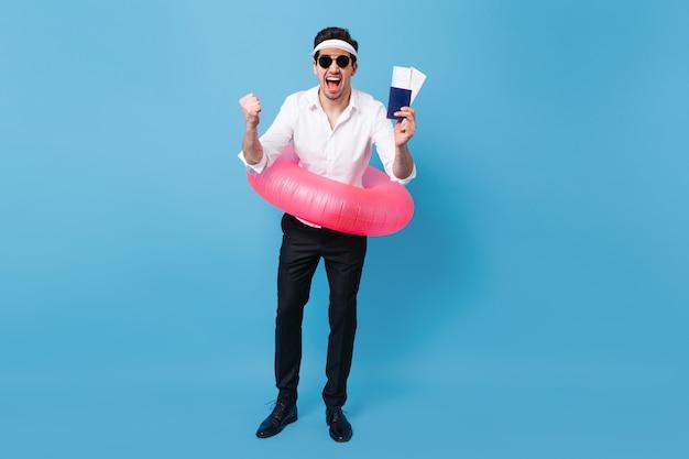 Volle länge des mannes, der urlaubsreise genießt. kerl im geschäftsanzug und in der sonnenbrille, die dokumente, tickets und rosa aufblasbaren kreis halten.