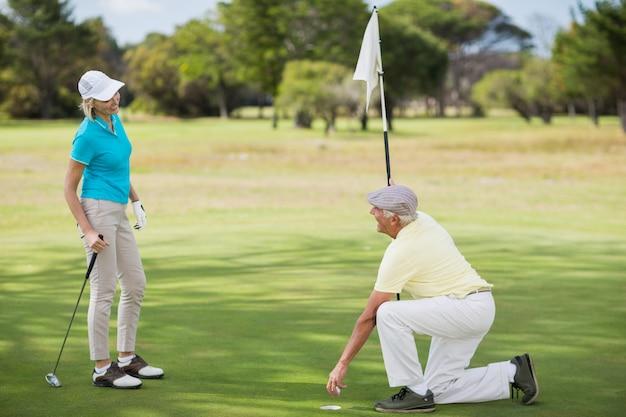 Volle länge des paares, das golf spielt