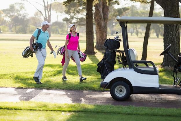 Volle länge des reifen golferpaares durch golfbuggy