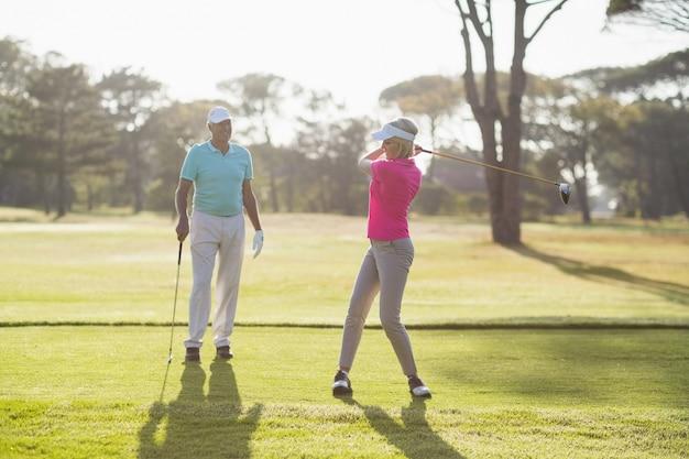 Volle länge des reifen golfers, der vom mann spielt