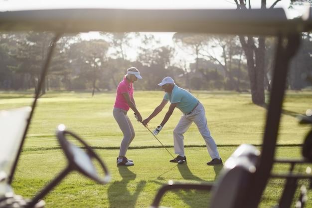 Volle länge des reifen mannes, der frau lehrt, golf zu spielen