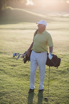 Volle länge des reifen mannes, der golftasche trägt