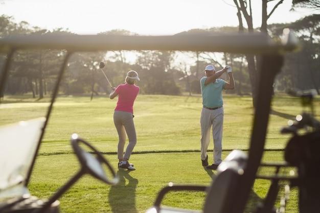 Volle länge des reifen paares, das golf spielt