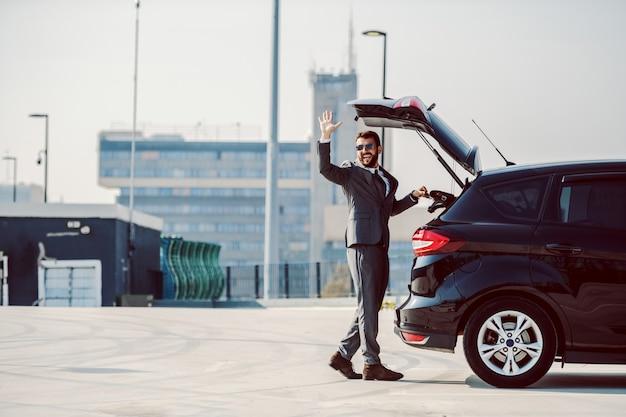 Volle länge des schönen kaukasischen bärtigen geschäftsmannes mit sonnenbrille, die seine ledertasche vom kofferraum nimmt und winkt.
