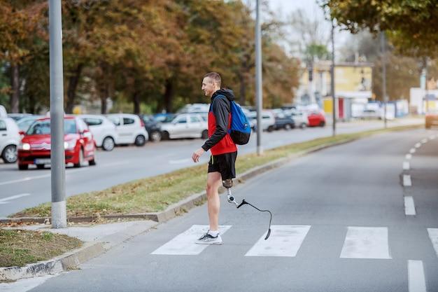 Volle länge des schönen kaukasischen behinderten sportlers in der sportbekleidung, mit künstlichem bein und rucksack, die straße überqueren.