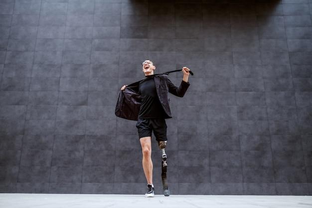 Volle länge des schönen kaukasischen geschäftsmannes mit künstlichem bein, das der arbeit müde wird und seinen anzug zerreißt, während er draußen vor der grauen wand steht. es ist zeit für sport.