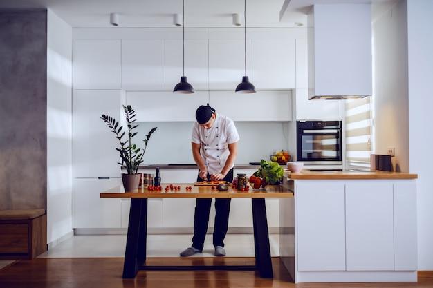 Volle länge des schönen kaukasischen kreativen kochs, der in der küche steht und lachs zum mittagessen schneidet. auf der küchentheke stehen gemüse und gewürze.