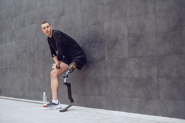 Volle länge des schönen kaukasischen sportlers mit künstlichem bein, das an wand anlehnt und vom laufen ruht. neben ihm steht eine flasche mit erfrischung.