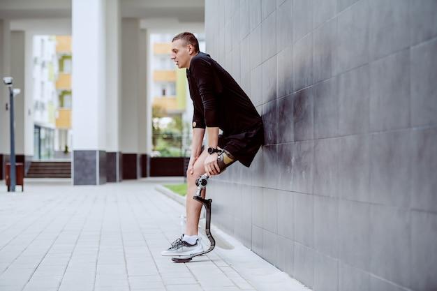 Volle länge des schönen kaukasischen sportlers mit künstlichem bein, das an wand anlehnt und vom laufen ruht.