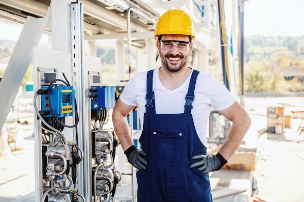 Volle länge des schönen kaukasischen unrasierten lächelnden arbeiters insgesamt und mit helm auf dem kopf, der neben armaturenbrett in der raffinerie aufwirft.