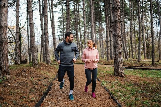 Volle länge des sportlichen paares in form, das im herbst durch wälder läuft und sich gegenseitig ansieht.