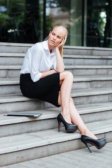 Volle länge einer blonden jungen frau, die auf der treppe mit laptop sitzt und wegschaut