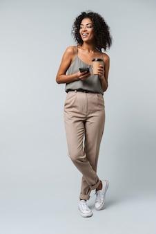 Volle länge einer glücklichen jungen afrikanischen frau, die lässig gekleidet steht, isoliert steht, auf handy spricht und tasse zum mitnehmen hält