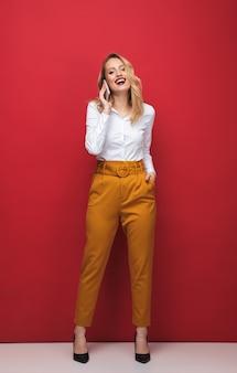 Volle länge einer glücklichen schönen jungen blonden frau, die lokal über rotem hintergrund steht und handy hält