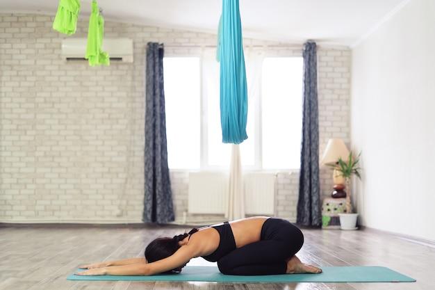 Volle länge einer jungen frau, die in kinderpose auf einer yogamatte sitzt
