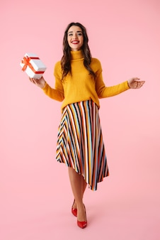 Volle länge einer schönen jungen frau, die bunte kleidung trägt, die lokal über rosa steht und geschenkbox hält