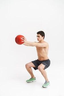Volle länge eines selbstbewussten jungen hemdlosen sportlers, der übungen mit schwerem ball über weiß macht