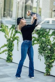Volle länge junge blonde mode und 0 kaukasische frau hält einen kleinen lustigen hund in den armen von zwei farben schwarz-weiß-chihuahua. umarmungen und küsse liebe. fröhliche emotionen.