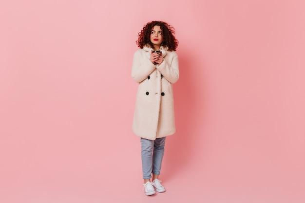 Volle länge schuss der jungen lockigen frau mit den roten lippen, die weißen mantel und jeans tragen glas des tees auf rosa raum tragen.