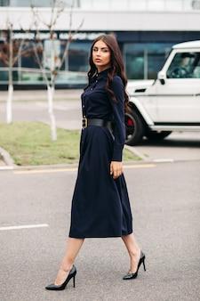 Volle länge schuss der jungen schönen eleganten dame, die schwarzes kleid trägt und auf stadtstraße geht. stil und modekonzept