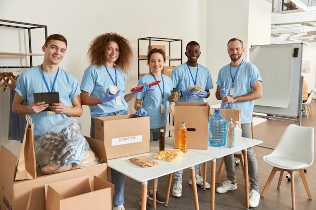 Volle länge von freiwilligen, die in die kamera lächeln, während sie lebensmittel in kartons sortieren