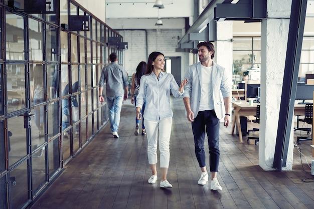 Volle länge von jungen modernen menschen in schicker freizeitkleidung, die eine diskussion führen, während sie durch das büro gehen