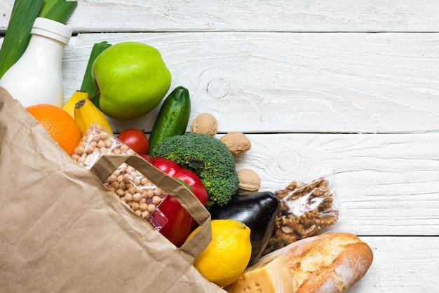 Volle papiertüte mit verschiedenen gesunden vegetarischen lebensmitteln auf weißem holzhintergrund. obst, gemüse, nüsse, brot und milch