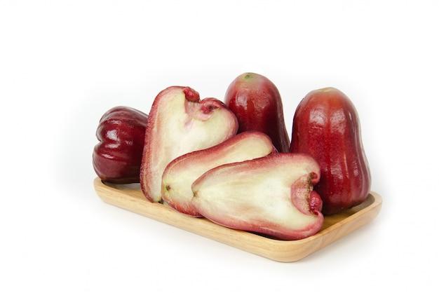Volle schärfentiefe. gruppe rosen-apfel- oder java-apfel- oder syzygiumsamen mit geschnittenem und voll auf hölzernem behälter. isoliert auf weißem hintergrund. fruchtaromen von süßem rotem glanz. frisches obst.