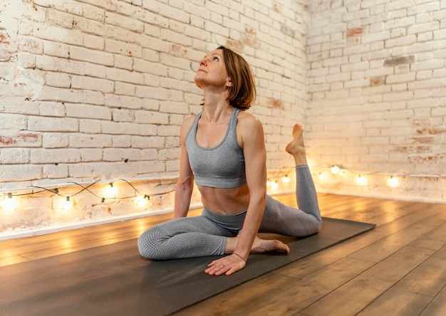 Volle schuss alte frau auf yogamatte