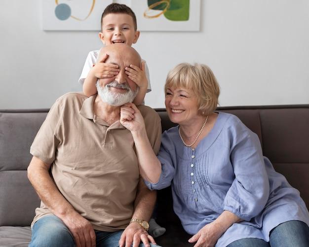 Volle schuss glückliche familie, die auf couch sitzt