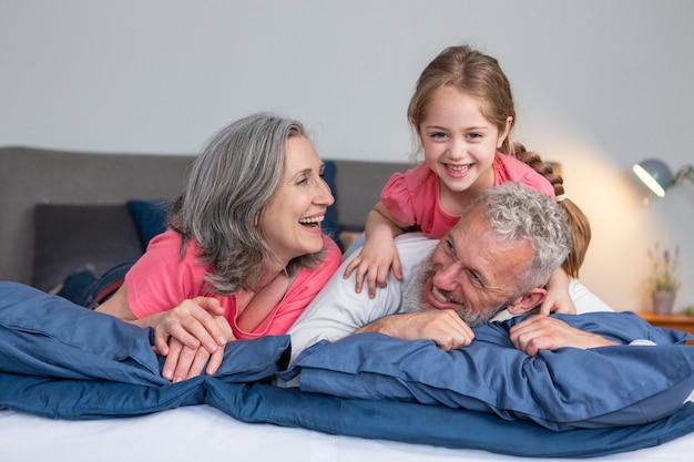 Volle schuss glückliche familie, die im bett spielt