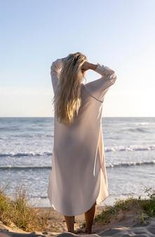 Volle schussfrau, die am strand aufwirft