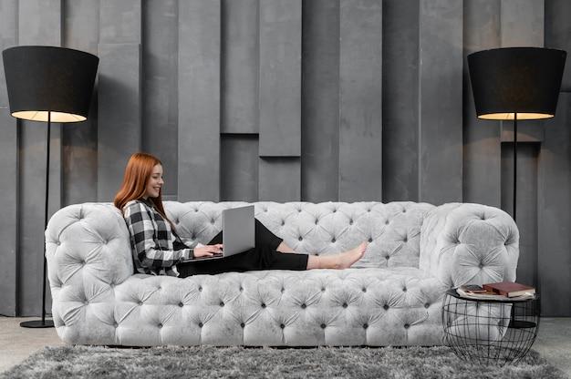 Volle schussfrau, die auf couch sich entspannt