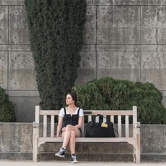 Volle schussfrau, die auf einer bank sitzt