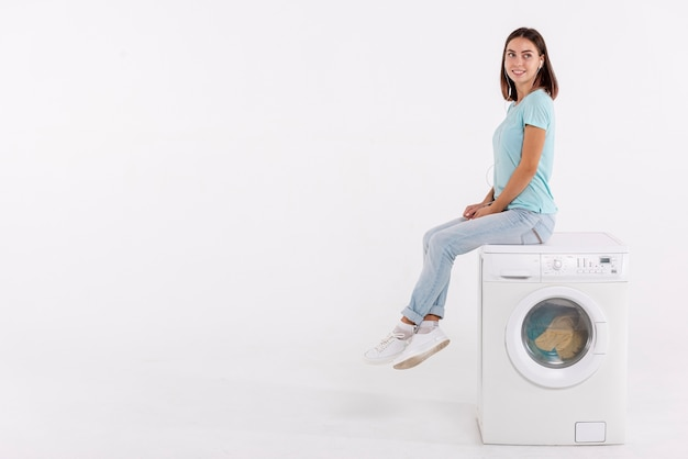 Volle schussfrau, die auf waschmaschine aufwirft