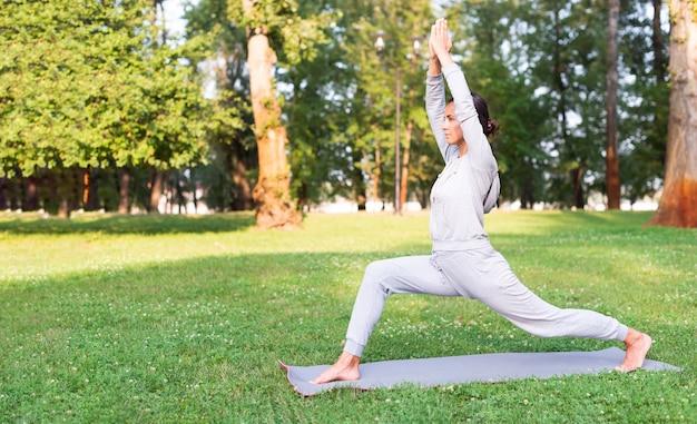 Volle schussfrau, die auf yogamatte ausdehnt