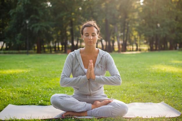 Volle schussfrau, die auf yogamatte meditiert