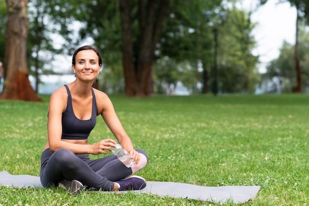 Volle schussfrau, die auf yogamatte sitzt