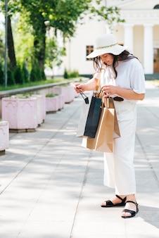 Volle schussfrau, die eine einkaufstasche untersucht