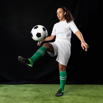 Volle schussfrau, die fußball spielt