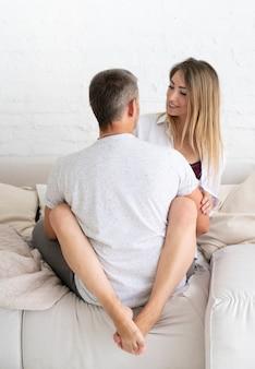 Volle schussfrau, die ihren ehemann betrachtet