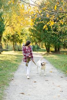 Volle schussfrau, die mit ihrem hund geht