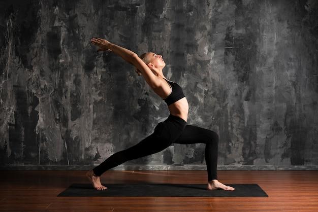 Volle schussfrau, die yoga auf matte tut